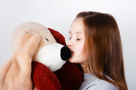 teen girl kissing a toy dog in the nose photo