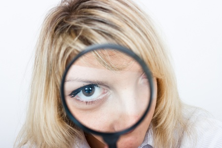 Girl is looking through a magnifying glass photo