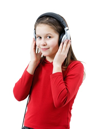 A smiling child girl listens to music through headphones on the white background photo