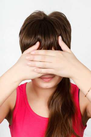 Young attractive girl closes her eyes with her hand photo