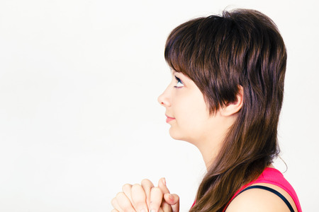 Young attractive girl praying with clasped hands together Stock Photo - 25335849