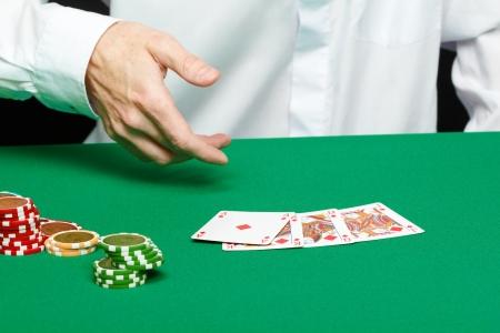 jugador. Mano masculina con las cartas y fichas en la mesa verde photo