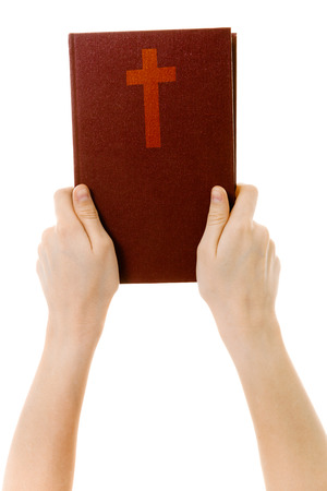 on a white background childrens hands holding a bible Stock Photo
