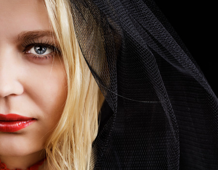 portrait of blue-eyed blonde young woman in a black veil photo