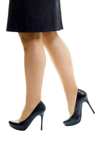 Female legs in skirt and high heels. White background. isolated photo