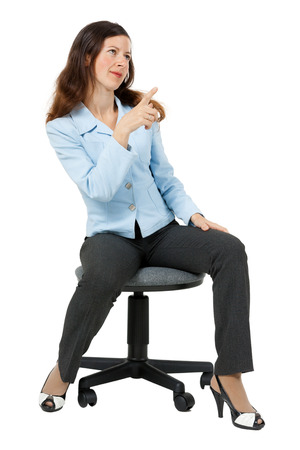 Young woman points at something sitting on an office chair photo