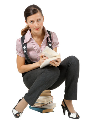 Young woman reading sitting on a pile of books photo