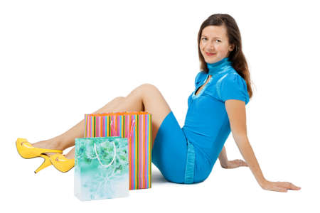 Young woman with packages sitting on the floor photo