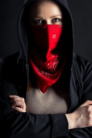 On a black background girl formidable form in black hood with a red shawl on his face photo