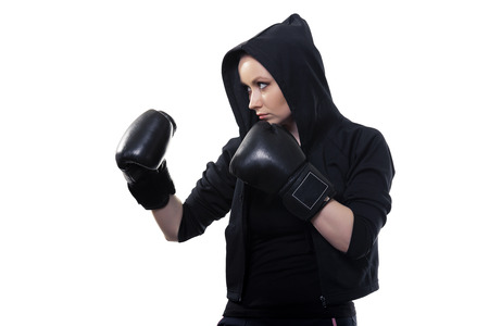 Young serious woman in boxing gloves on a white background photo