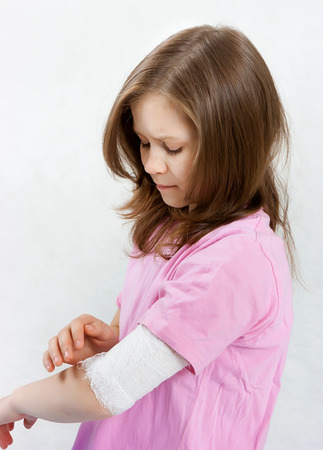 Childhood trauma. A child with a bandage tied hand photo