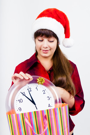 Young blue-eyed beautiful girl in santa hat with clock photo