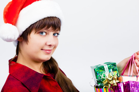 Young blue-eyed beautiful girl in santa hat with presents photo