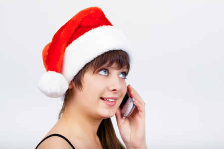 Young blue-eyed beautiful girl in santa hat with phone photo