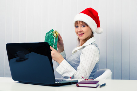 Attractive girl in the office in Santa hats with a laptop and a gift photo