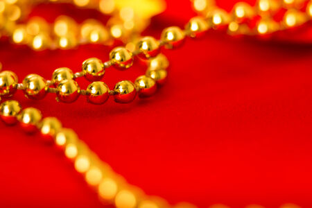 Gold beads on red fabric. macro shooting photo