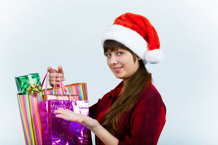Attractive young woman in santa hat with holiday shopping photo