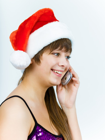 Attractive young woman in santa hat talking on the phone photo
