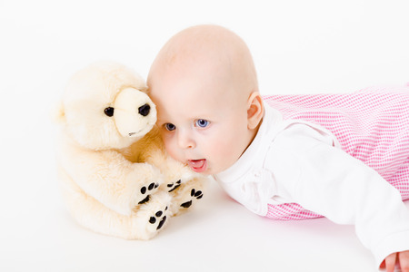 blue-eyed baby with a soft toy.  Stock Photo