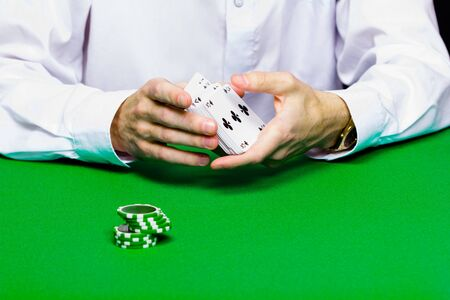 card player: Card player shuffles the cards. green table Stock Photo