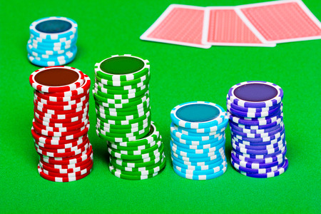 Stack of chips on the background of green the table. Cards in the background photo