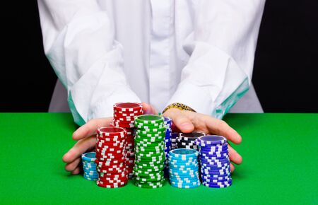 Man puts in the casino. Hand with chips closeup photo