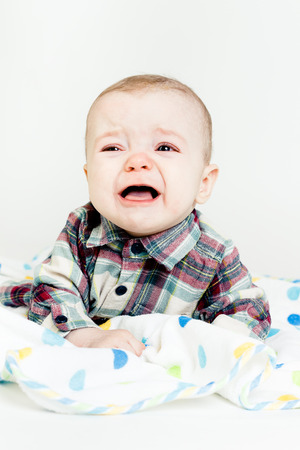 Adorable baby screaming in a plaid shirt photo
