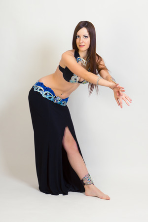 full height: young woman dressed as a performing belly dancing. Studio. full height