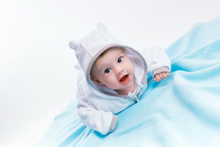 blue blanket: Cute baby in the hood on a blue blanket