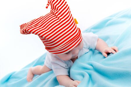 blue blanket: beautiful baby in the cap on a blue blanket Stock Photo