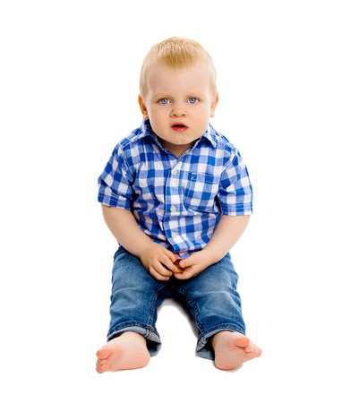 discontented: Little dissatisfied boy in a plaid shirt and jeans on white background Stock Photo