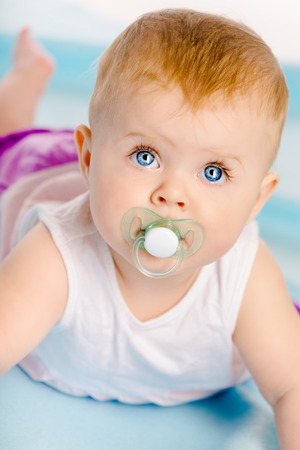 Beautiful blue-eyed baby with a pacifier. Close-up. Studio photo