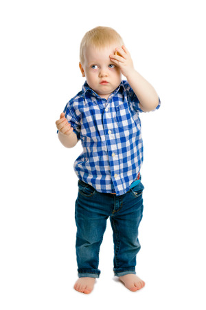 woe: baby boy standing on a white background. headache