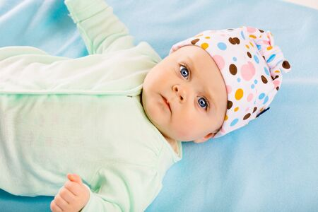 blue blanket: Portrait of a baby in a cap on a blue blanket