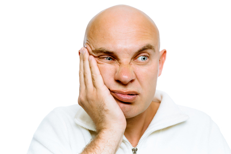cheek: Bald man holding his hand to his cheek. Toothache or problem