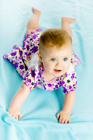 creep: blue-eyed baby girl in a dress creeps on the blue coverlet