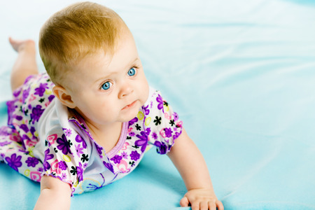 coverlet: blue-eyed baby girl in a dress creeps on the blue coverlet
