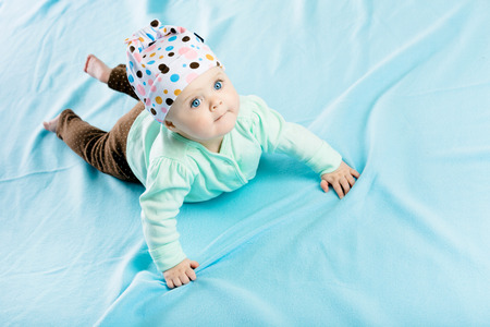coverlet: The blue-eyed baby in hat crawling on the blue coverlet Stock Photo