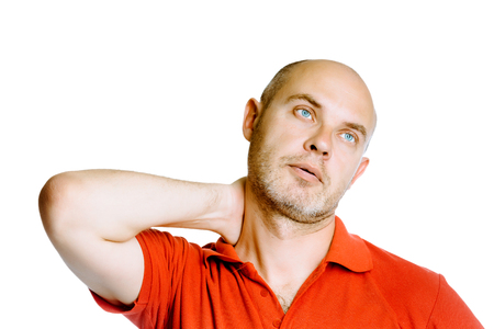 Unshaven blue eyed middle-aged man holding his neck. Pain. Studio. isolated