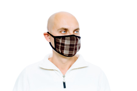 pandemic: Bald, blue-eyed man in a white jacket and mask. Studio. isolated