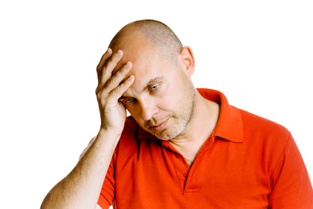 unshaven: Unshaven blue eyed middle-aged man holding his head. Headache. Studio. isolated