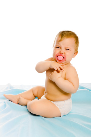 coverlet: upset baby in diapers on a blue coverlet. Studio Stock Photo