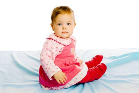 blue blanket: Beautiful baby girl sitting on a blue blanket. Studio