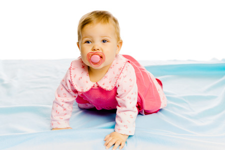 Beautiful baby girl with pacifier crawling on the blue coverlet. Studio Stock Photo