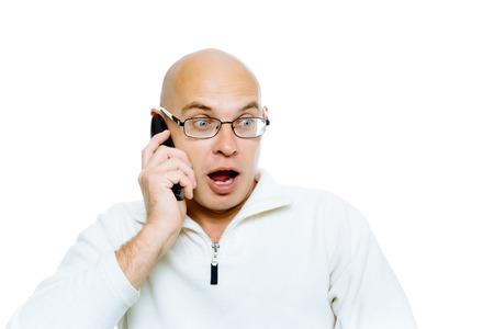 communicates: Bald man emotionally communicates by phone. Isolated on white. Studio Stock Photo