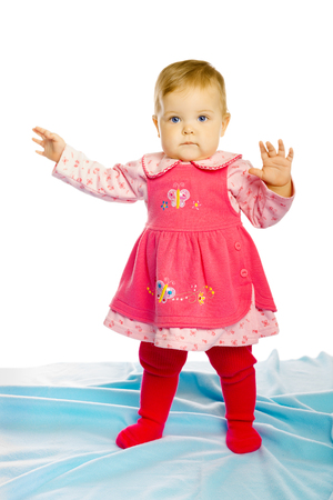 full height: baby girl in a dress standing in a full height and looking at the camera