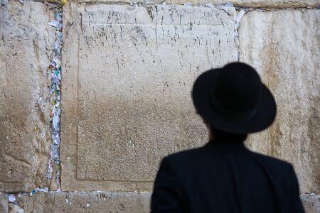 hebrew script: Praying man in Jerusalem Western Wall