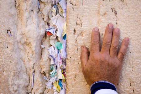 jewish ethnicity: Hand with shoulder of praying men on the Western Wall with wishes in Jerusalem.