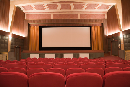 Empty retro cinema auditorium in cubism style with line of chairs and projection screen. Ready for adding your own picture.