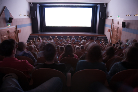Cinema auditorium with people in chairs watching movie performance. Ready for adding your own picture. Standard-Bild